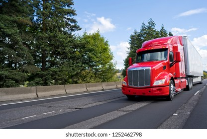 Bright red bonnet American modern long haul big rig semi truck with dry van semi trailer transporting commercial cargo moving on the wide multiline green highway road