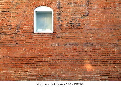 a bright red brick building wall with one single white arched window