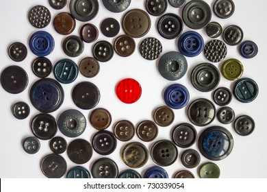 A bright red button for clothes among other black, dark buttons. Confrontation, loneliness, violation of rules and dress code. White background, top view.