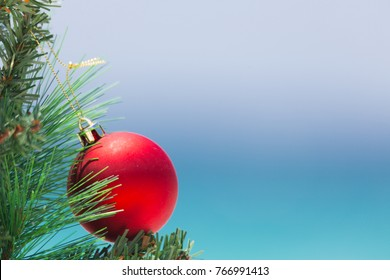 A bright red Christmas bauble hangs on a tree with a beautiful blue sky and ocean backdrop