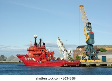 Bright Red Diving Support Vessel loading supplies in port.