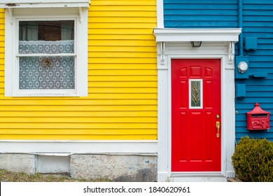 A bright red door of a building with blue and yellow wooden clapboard walls. The house has a red decorative metal mailbox. There's a green shrub near the red door with white trim.