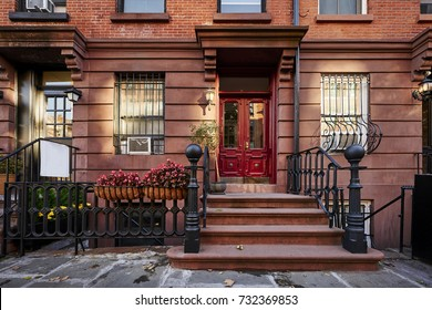 A bright red door and colorful flowers on a brownstone in a neighborhood of Manhattan, New York City.