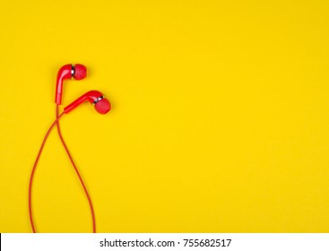 Bright red earbud headphones isolated on a bright yellow background with copy space on the right for your text (minimal concept, top view)