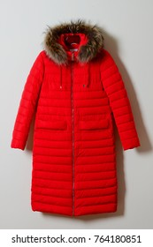 Bright red female winter jacket with a hood on fur, with a zipper. Outerwear. A long female jacket, isolated on a white background.