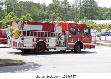 A bright red fire truck on duty in a parking lot