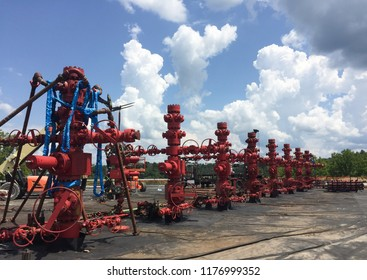 Bright Red Frac Stack at Hydraulic Fracturing Site Against Big Blue Sky