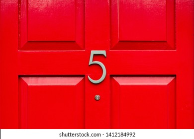 Bright red front door with the house number 5 and the five in elegant Silver metal with a peep hole den close up