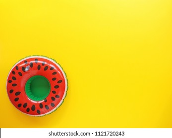 Bright red and green pool float on yellow background with space for text