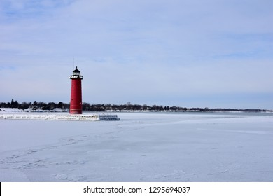 Bright red harbor marker in Kenosha Wisconsin at the end of an ice covered pier on a cold January day.
