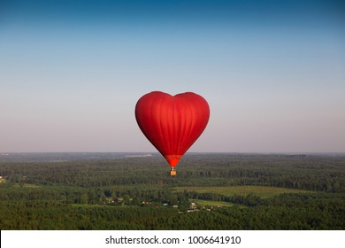 Bright red Heart shaped air balloon in the sky.
