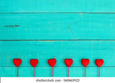Bright red hearts border antique rustic teal blue wood background; Valentine's Day and love concept with copy space