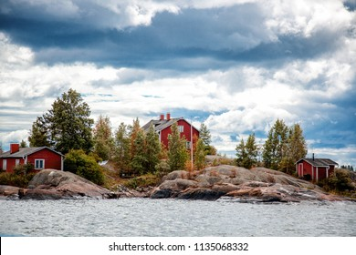 Bright red houses on the rocks on a small island near Helsinki. Beautiful scenery in cloudy weather