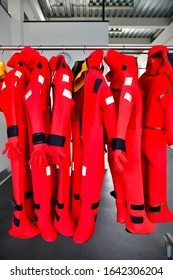 Bright red immersions suits hanging neatly in a row giving a nice esthetic look