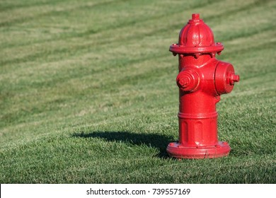 Bright red isolated fire hydrant sits in a freshly cut grass field.