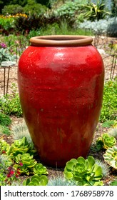 Bright red, large decorative ceramic jar is a focal point in a garden flowerbed. Home decor idea for garden decoration.