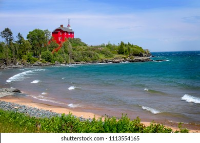 Bright red lighthouse along the shores of Lake Superior in Marquette, Michigan. Surrounded by a swooping shoreline and striking teal blue water.