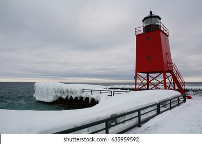 A bright red lighthouse contrasts against an overcast sky and snow covered pier on Lake Michigan.