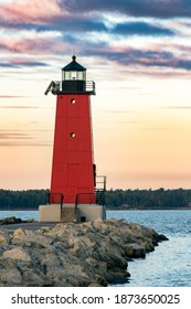 A bright red lighthouse glows in the light of sunrise at Manistique on the Lake Michigan coast of Upper Peninsula Michigan with colorful clouds above.