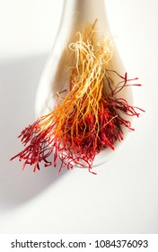 Bright red and orange color saffron in white spoon. Famous Fineeat quality Persian saffron.