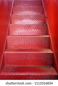 bright red painted metal staircase with steps made of steel plate with a textured surface and smooth metal walls