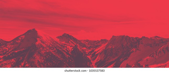 Bright red panoramic alpine landscape with artistic color effect over snowy winter mountain peaks and steep valleys