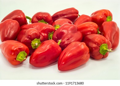 Bright red peppers with green tails on white background.