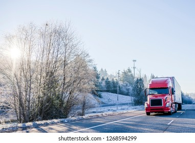 Bright red popular big rig bonnet semi truck with refrigerator semi trailer transporting perishable and frozen food cargo on straight winter highway with snow frosty hill trees