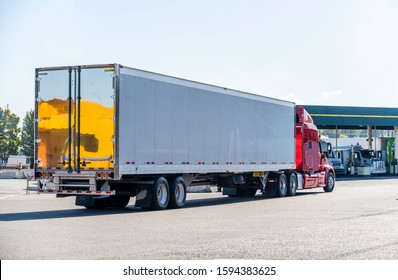 Bright Red powerful big rig American long haul semi truck with dry van semi trailer driving on the truck stop parking lot to fuel station for refueling