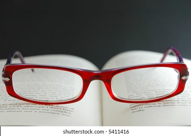 Bright red reading glasses on open book - focus on glasses