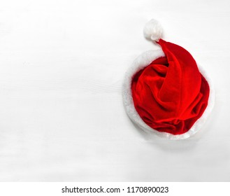 Bright red Santa Claus hat on wooden background. Top View Flat Lay Group Objects