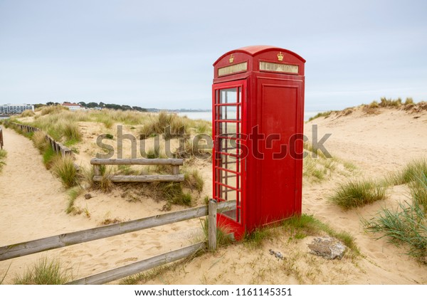 A bright red telephone box on the sand dunes at South Haven Point in Dorset at the end of the 630 mile South West Coast Path in England, UK.