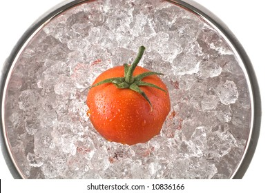 Bright red tomato resting in metal bowl of ice, isolated on white