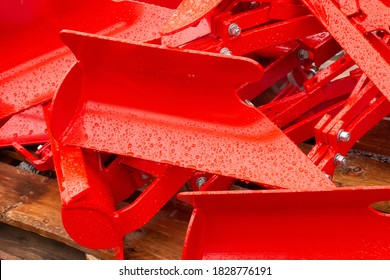 Bright red Tractor accessory parts in rain awaiting construction.