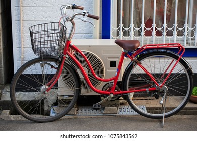 Bright red traditional Japanese mamacheri bicycle on side of road