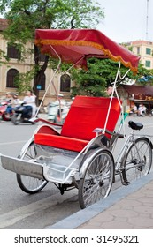 A bright red Vietnamese cyclo parked by road side with busy traffic