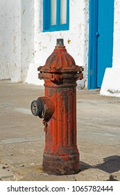 A bright red water hydrant with clapper valve, old white painted building with flaking paint and bright blue door and window.