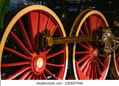Bright red wheels of old locomotive on railway tracks closeup. Absract vintage background