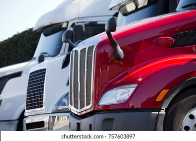 Bright red and White Big rigs semi trucks of different makes and models stand in row on truck stop parking lot for truck driver rest according to logbook delivery schedule