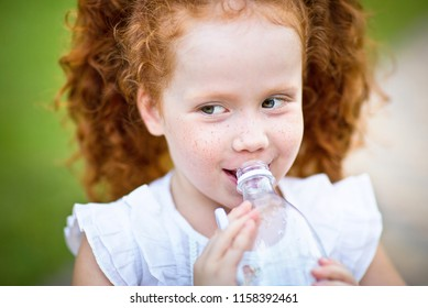 Bright red-haired little girl drinking water