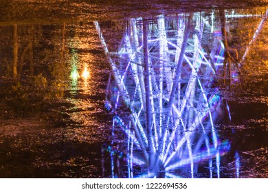 A bright reflection of the observation wheel in the dark river water in a quiet autumn evening.