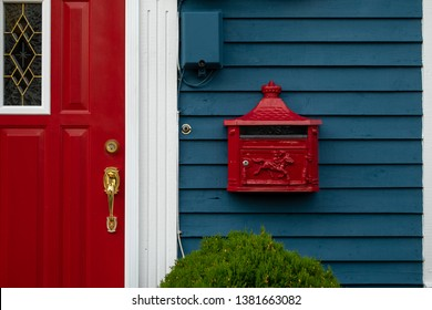 A bright retro looking red mailbox, or letterbox, affixed to the exterior wall of a blue wooden house made of clapboard. There's a red door with gold door knob and white trim on the building.