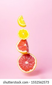 Bright ripe juicy sliced lemon and grapefruit hang in the air on a pastel pink background. The concept of a healthy lifestyle, vitamin C. Minimalism, place for text. Levitation.