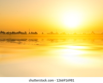 Bright rising sun over fields and water surface. Autumn morning.