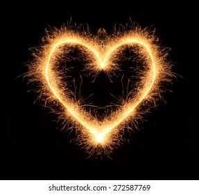 Bright romantic love heart drawn with sparkles isolated on black background