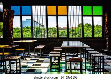 The bright room with color glass. Chairs and tables in the stained glass room. A room with external light through a window decorated with color patterned glass or figured glass.