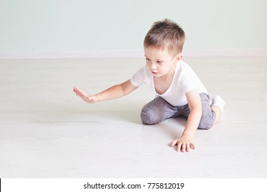 bright room. happy boy playing on the floor. A boy in a white t-shirt