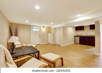 Bright room with new hardwood floor and ivory walls. Tropical style furniture set with dry branches in the corner. View of kitchen area with dark brown cabinets. Mother-in-law apartment