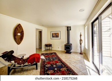 Bright room with resting area and antique stove. Colorful rug on the tile floor and resting chair with small table. Room decorated with handmade art