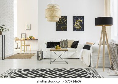 Bright room with white sofa, table, pattern carpet and lamp